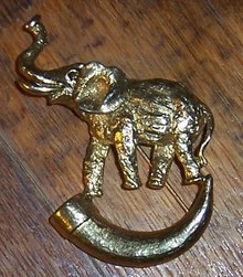 Vintage Gold Tone Pin Elephant with Raised Trunk Standing on a Horn