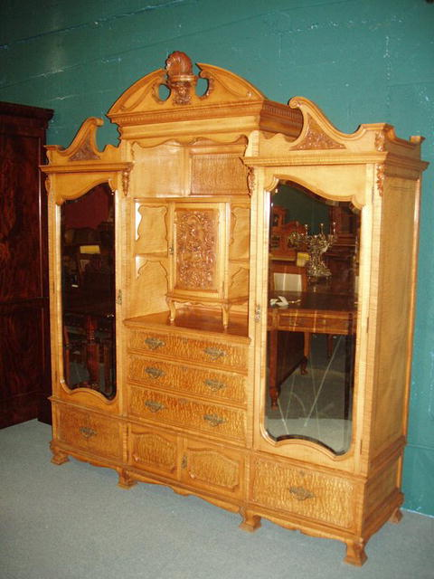 An excellent quality English 19th century Armoire in Satinwood with finely detailed carving.