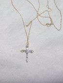 A Ladys White Diamond and Gold Cross Pendant