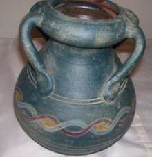 A Large green pottery vase with 4 applied handles, hand turned clay vase