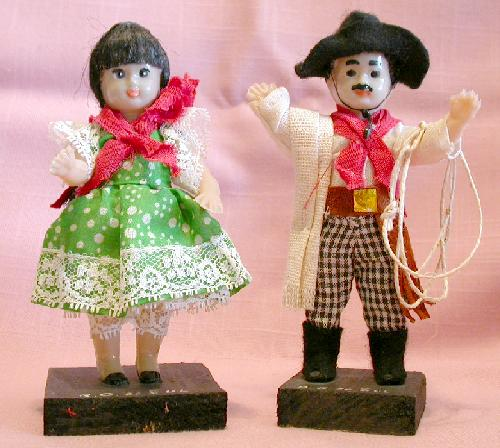 PAIR OF LATIN LOOKING DOLLS ON WOOD STANDS
