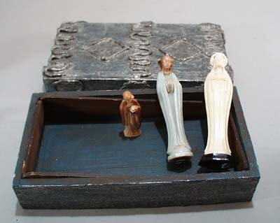 Wooden box holding 3 little statues of Christ and Mary