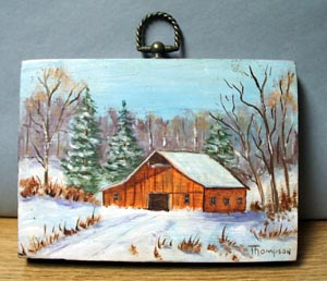 Old barn scene in snow painted on piece of board.