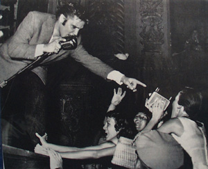 Picture of Elvis With Mike and Pointing to Fan 1956