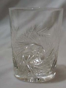 Cut glass tumbler with starburst design.