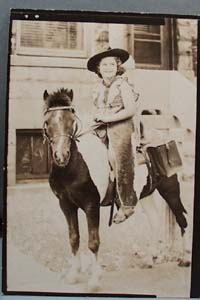 Old photo of young girl on pony with costume