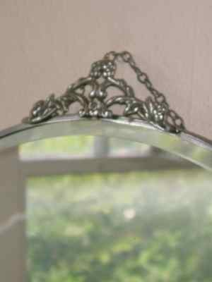 Beveled Oval Mirror with Floral & Leaf Chrome Crest
