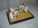 Miniature Japanese Basque Porcelain Man and Woman on Bamboo Mat