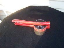RED HANDLED POTATO RICER OR MASHER
