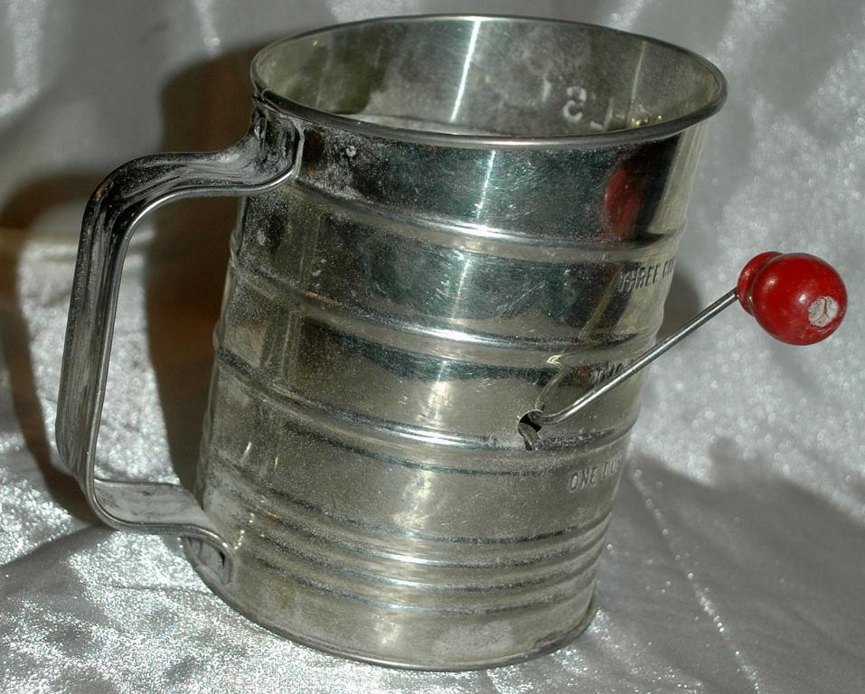 Bromwell's tin flour sifter with a  red painted wooden sifter handle