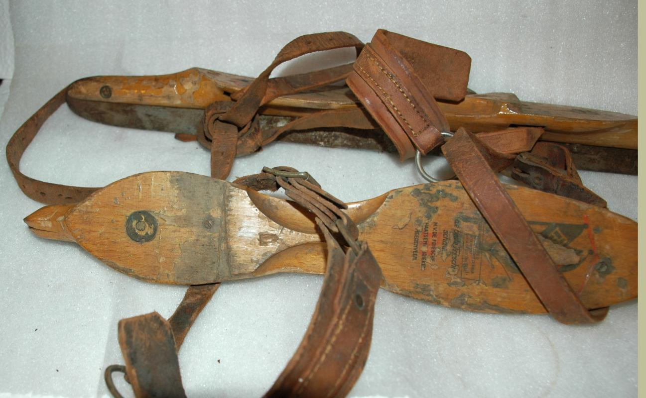 A pair of antique wooden ice skates from Amsterdam with leather straps.